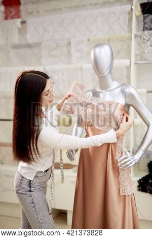 Professional Brunette Dressmaker, Tailor Or Seamstress Working With Model Applying Textile Cloth On