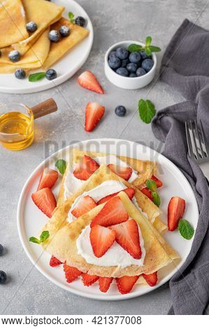 Crepes Or Thin Pancakes With Cream Cheese, Fresh Strawberries And Honey On A White Plate On A Gray C