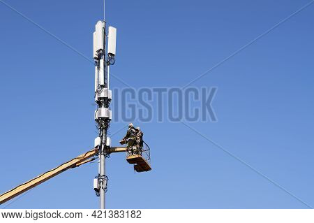 Installation Of A Cellular Communication Tower. Workers At A Height Install The Equipment. Copy Spac