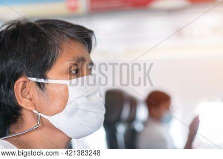 Elderly Asian Female Passenger Wearing Face Mask While On Aircraft While Protect Coronavirus Epidemi
