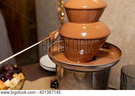Chocolate Fountain For A Birthday Or Wedding. Dipping A Banana Into A Chocolate Fountain.