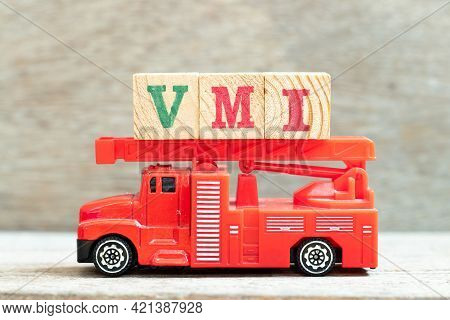 Fire Ladder Truck Hold Letter Block In Word Vmi (abbreviation Of Vendor Managed Inventory) On Wood B