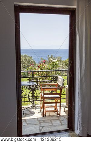 View Of The Open Balcony Doors With A View Of The Aegean Sea In Greece Island.