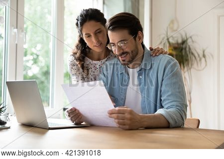 Happy Affectionate Young Family Couple Reading Paper Correspondence.