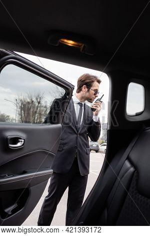 Bodyguard In Sunglasses Using Walkie Talkie Near Modern Car.