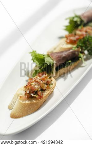 Mixed Tapas Plate With Tomato Bruschetta And Serrano Cured Ham On White Table