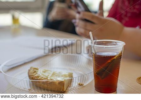 A Plastic Cup With A Bagged Tea Stands Next To A Pie On A Plate On The Office Table Next To The Silh