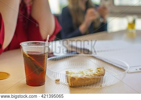 A Cup Of Bagged Tea And A Piece Of Sweet Cake Lie On The Office Table Against The Background Of Two