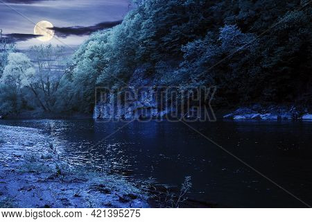 River Flow Under The Rock At Night. Beautiful Nature Landscape In Spring. Deciduous Trees On The Sho