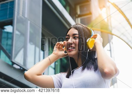 Happy Young Woman Using Headphone For Listening Nice Music In City With Building Background And Toot