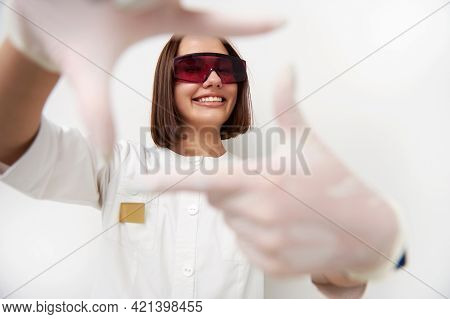 Focus On Beautiful And Happy Female Doctor Smiling With Toothy Smile While Looking Through Frame Mad