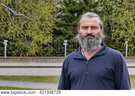 A Man Of 50 Years With A Gray Beard. Day, Horizontal Shot Front View. Surgut, Russia - 17, May 2021.