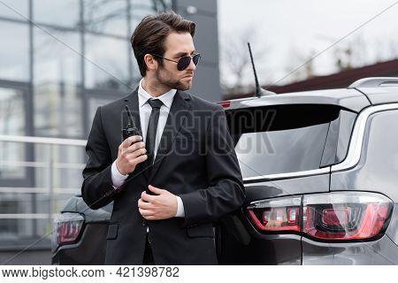 Side View Of Bodyguard In Sunglasses Holding Walkie Talkie Near Modern Car.