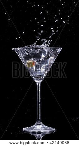 Martini drink splashing out of glass, isolated on black background