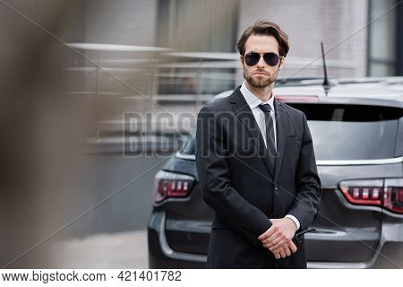 Bodyguard In Sunglasses And Suit Standing With Walkie Talkie Near Modern Car.