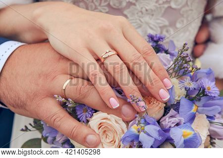 Hands Of The Newlywed With Gold Wedding Rings On The Background Of A Bouquet Of Blue Irises And Beig