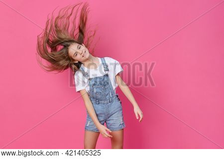 White Girl 10 Years Old In A White Top Waving Long Hair, Having Fun On A Pink Background, Emotions,