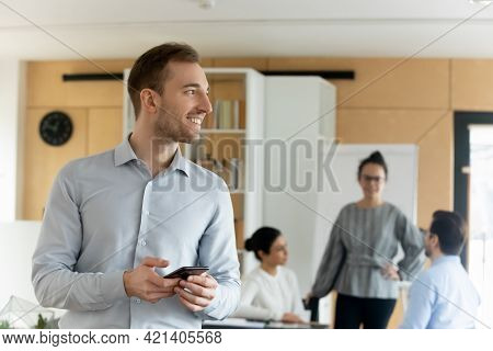 Smiling Confident Dreamy Caucasian Young Businessman Distracted From Phone