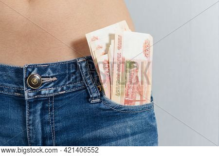 From The Front Pocket Of The Girl's Jeans Stick Out Buy 5 Thousand Russian Rubles. Horizontal Photo