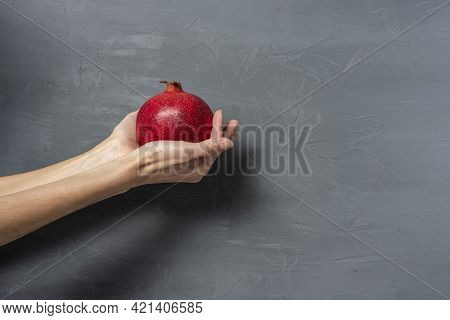 On A Gray Textured Background, A Woman Holds A Ripe Red Pomegranate In Her Hands. Copy Space, Text S