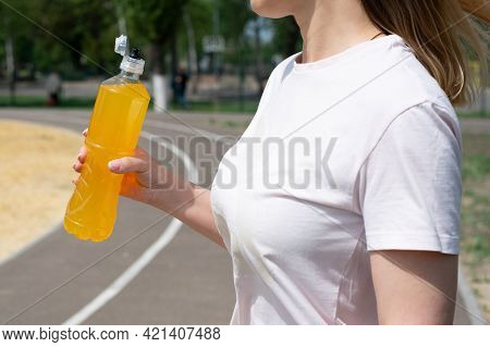 Sportswoman In White T-shirt Holding Bottle With Orange Isotonic Drink On Sports Ground, Summer, Clo