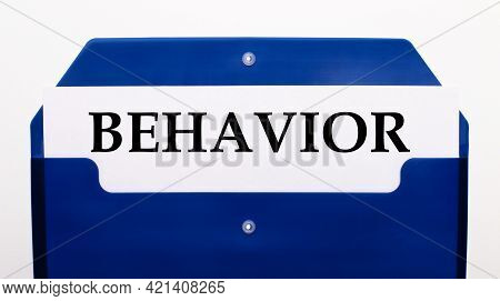 On A White Background, A Blue Folder For Papers. In The Folder Is A Sheet Of Paper With The Word Beh