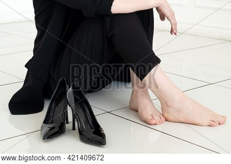 Pretty Young Woman In Black Business Suit Sits On The Floor With Her Bare Feet, High-heeled Shoes Ne