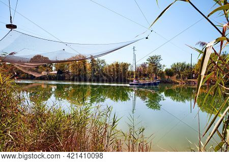 Ravenna, Emilia Romagna, Italy: Landscape Of The River With Net Of The Fishing Hut And Boat In The N