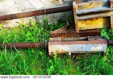Parts Of A Metalworking Industrial Machine Covered With Rust, Abandoned And Overgrown Grass
