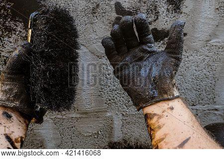 Waterproofing Worker Hands In Gloves With Brush In Bitumen Mastic. Protective Waterproofing Coating
