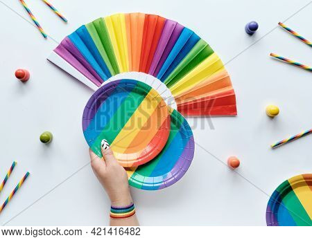 Lgbtq Community Pride Month Rainbow Concept Flat Lay. Hand With Ribbon Holds Paper Plate. Rainbow Fa