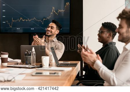 Colleagues Having Meeting In Boardroom, Clapping Hands