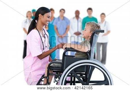 Nurse chatting with little boy in wheelchair with medical staff in background