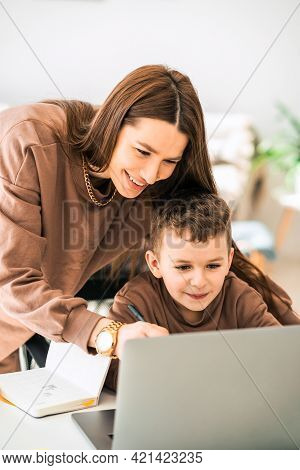 Happy Mother Helps Her Little Son With Online Homework On Laptop. Distance Education