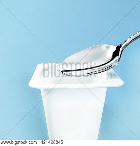 Yogurt Cup And Silver Spoon On Blue Background, White Plastic Container, Fresh Dairy Product For Hea
