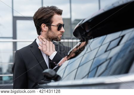 Bearded Bodyguard In Suit And Sunglasses Adjusting Security Earpiece Near Blurred Car.