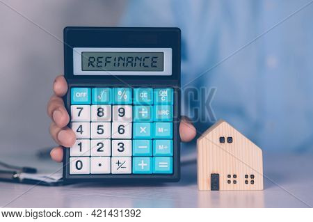 Hands Of Business Man Holding Calculator For Calculate Refinance Home And Expense For Loan Mortgage,