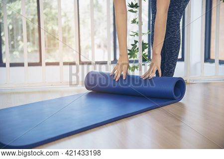Woman Hands Rolled Up Yoga Mat On Gym Floor In Yoga Fitness Training Room. Home Workout Woman Close