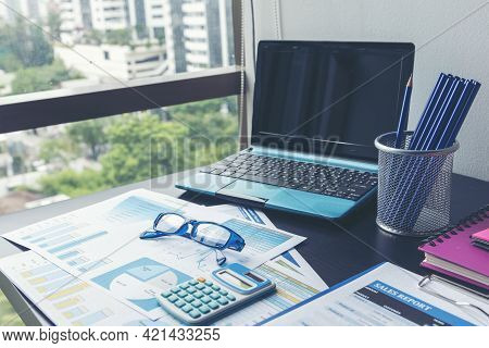 Office Laptop Business Financial Document Chart And Graph On Wooden Table With Coffee Cup. Flat Lay