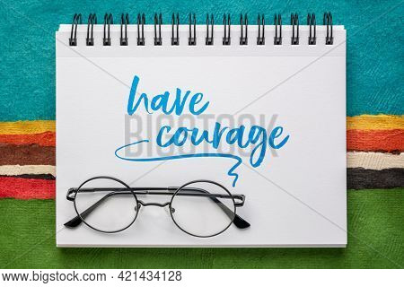 have courage inspirational message, advice or reminder, handwriting in a spiral notebook against abstract paper landscape, personal development concept