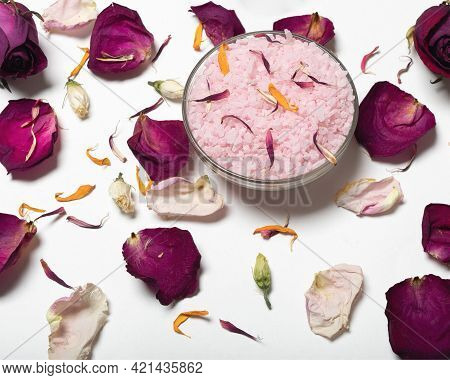 Pink Salt Surrounded By Rose Petals And White Towel On White Surface.
