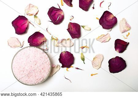 Himalayan Pink Salt And Flower Petals On White Background. Natural Cosmetics Concept With Aroma Spa