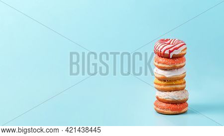 Stack Of Assorted Donuts On Blue Background. Many Colorful Glazed Doughnut With Sprinkles Stacked Wi
