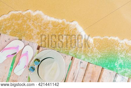Top View Of Pink-white Sandals, Straw Hat And Sunglasses On Wooden Bridge Over Emerald-green Sea Wat