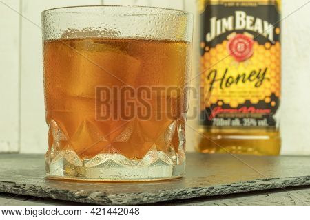 Warsaw, Poland - May 22, 2021: Glass Of Jim Beam Whiskey With Ice. Whiskey On Ice In A Large Glass A