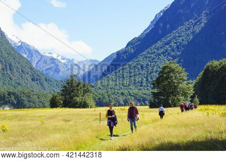 South Island New Zealand - March 5 2015; Tourists Walking In Line Long Grassy River Flat Between Con