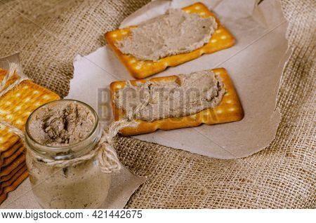 Defocus, Blur, Soft Focus. Rectangular Crackers And Glass Jar Of Liver Pate On Burlap. Close-up Of C