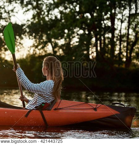 Relaxed Young Woman Looking Away While Kayaking In A Lake Surrounded By Nature On A Late Summer Afte
