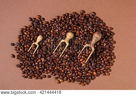 Roasted Brown Coffee Beans On Brown Background. Top View. Coffee Beans In A Wooden Scoop.