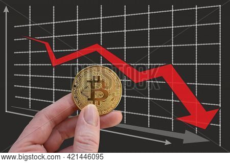 Hand Holds Bitcoin On Background Of Falling Graph With Red Arrow. Decrease In Exchange Rate. Red Arr